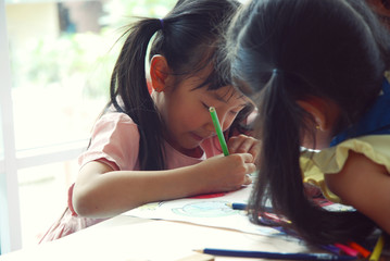 Girl child drawing on white paper to three children in holiday weekend.
