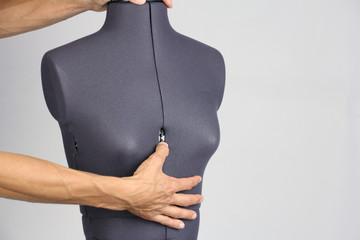 hands tailor change the size of the breast on a female sewing mannequin, gray background, copy space