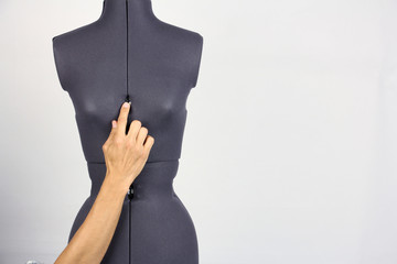 hands tailor change the width of the breast on a female sewing mannequin, gray background, copy space