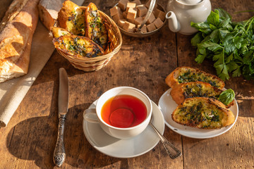Lunch - tea and traditional French baguette toast with butter, parsley, garlic and basil on an old rustic wooden table