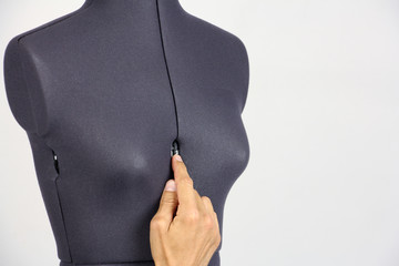 human hand change the size of the breast on a half-turned female sewing mannequin, gray background, copy space