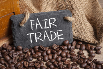 Kaffeebohnen mit Kaffeetasse und Kaffeemühle auf Holzbrett