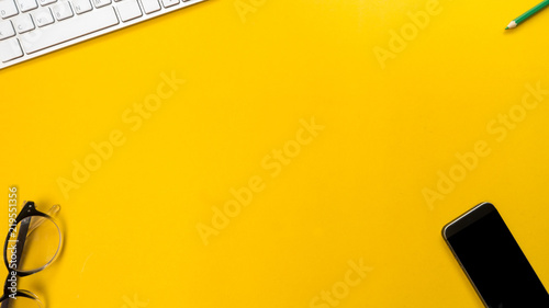 Wall mural Smartphone and keyboard with grass topview on yellow background business concept