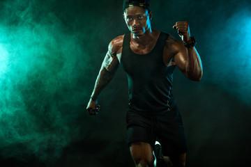 Sports men athlete runner on dark background. Power athletic guy bodybuilder doing fitness training. Man sprinter.