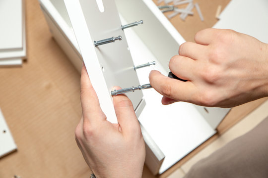 Assembling of furniture, closeup of tool in hand. Mounting screw is screwed into hole board.
