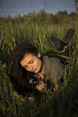 beautiful young girl in jacket lying down on grass