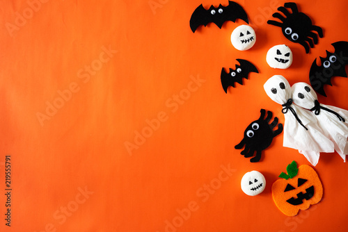 Top view of Halloween crafts, orange pumpkin, ghost and spide on orange background with copy space for text. halloween concept.