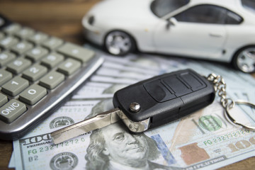 Car keys, money and calculator. The idea of buying a car, prices, insurance, expenses