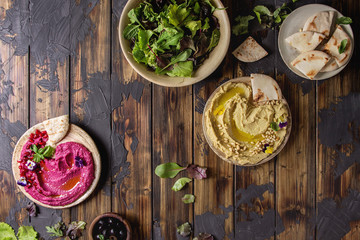 Variety of homemade traditional and beetroot spread hummus with pine nuts, olive oil, pomegranate served on ceramic plates with pita bread and green salad on dark wooden background. Flat lay, space.