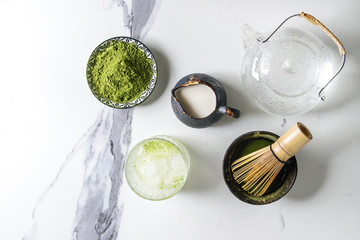 Ingredients for making matcha ice drink. Green tea matcha powder in ceramic bowl, traditional bamboo spoon, whisk, milk, glass teapot, ice cubes over white marble background. Flat lay, space