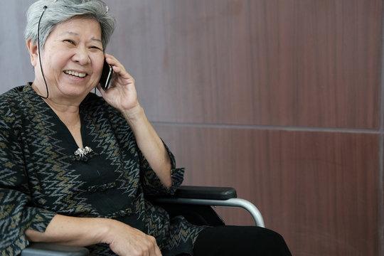 elder woman on wheelchair talk on mobile phone. elderly female speaking on smartphone. senior have phone conversation