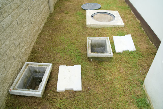 A man hole water and a hole of grease trap with the drain system around the house.