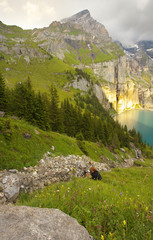 Mountain landscape with a lake of Oeschinensee with a photographer in action, Switzerland