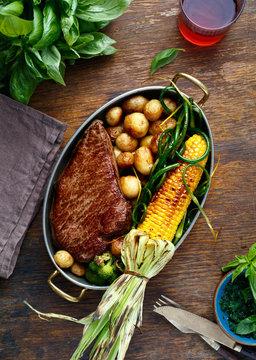 Beef steak frying pan fried corn potatoes green beans red wine top view