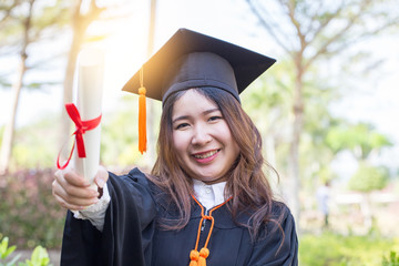 Beautiful Attractive Asian Women Student Graduate holding certificate in her hand and feeling so proud and happiness in Commencement day