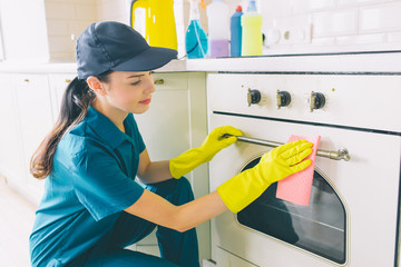 Nice and cheerful woman sits in squad position at stove and clean it door. She wears gloves and uniform for protection. Gir smiles a bit.