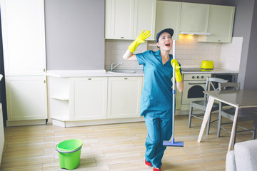 Fantastic woman stands in kitchen and holds mop in hands. She waves with hands and singing out loud. Cleaner has rest.