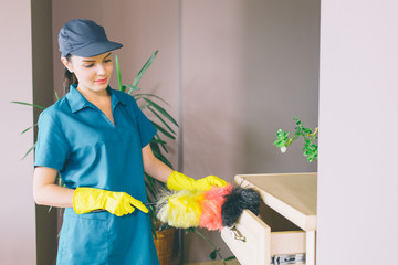 Another picture of girl stands and uses dust brush for cleaning drawer. She looks on it. Girl is concentrated. She wears blue uniform and yellow gloves.