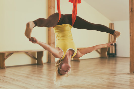 Woman doing aerial yoga in the fitness studio.