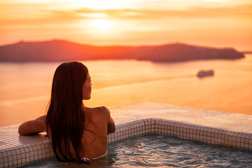 Wall Mural - Luxury wellness spa resort pool woman relaxing in jacuzzi swimming at sunset in Europe Santorini hotel travel destination. Summer holiday.