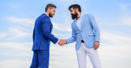 Men formal suits shaking hands blue sky background. Business deal approved accepted by both partners. Entrepreneurs shaking hands symbol successful deal. Sure sign you should trust business partner