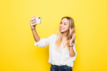 Portrait of woman take selfie holding phone in hand shooting selfie on front camera isolated on yellow background