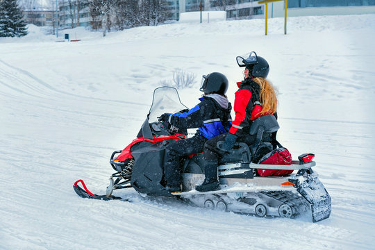 Woman and Man on Snowmobile at Winter Finland Lapland Christmas