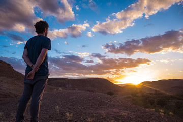 A young man watching the sunset in a beautiful valley. Some clouds in the sky, Beginning, reflection, relaxing, meditating, peaceful, insights concepts.