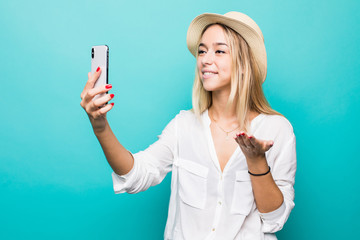 Portrait of young woman making video call on smartphone, waving at cam isolated over blue background