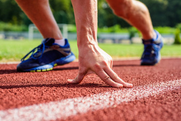 Runner ready to go close up. Ready steady go concept. At the beginning of great sport career. Hand touch track path close up. Hand of sportsman on running track low start position. Starting point
