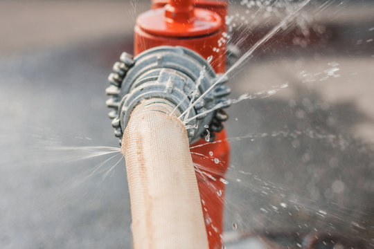 Damaged fire hose from a fire hydrant - water spray