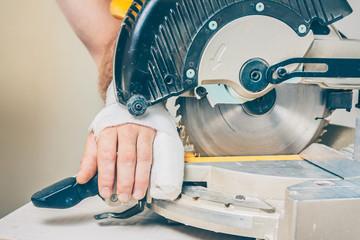 Bandaged damaged arm near the circular saw