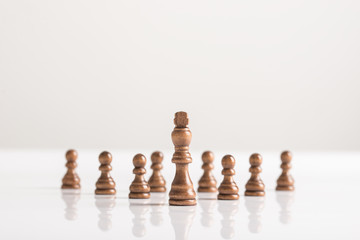 Dark chess pieces standing on white table