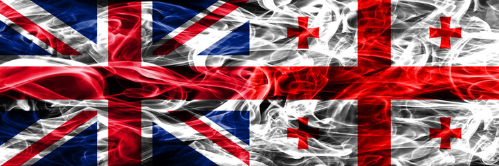 United Kingdom vs Georgia smoke flags placed side by side. Thick colored silky smoke flags of Great Britain and Georgia