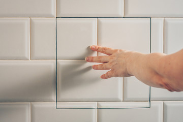 The girl opens a hidden hatch on the wall of the tile to access the inspection hole of the sewer pipe to eliminate clogging and cleaning