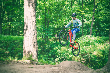 Cyclist in helmet on an orange bike doing a trick in a springboard jump in the forest, motion blur