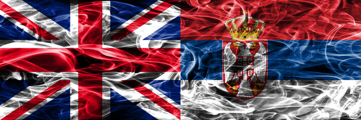 United Kingdom vs Serbia smoke flags placed side by side. Thick colored silky smoke flags of Great Britain and Serbia