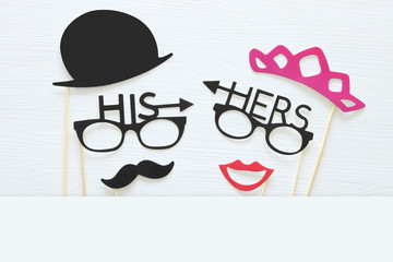 Top view image of funny photo booth props with text: HIS, HERS for party or wedding over white background.