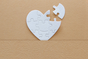 Top view image of paper white heart puzzle with missing piece over brown pastel background. Health care, donate, world heart day and world health day concept.
