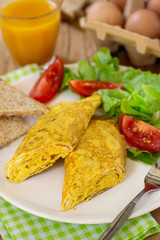 Rolled omelette with cheese served with vegetable salad