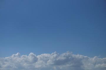 Weiße Wolken am Horizont und blauer Himmel - Stockfoto