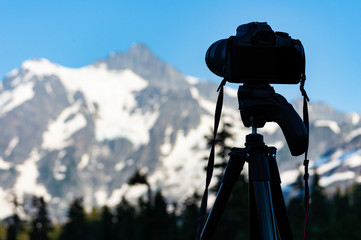 Camera on tripod taking photo of mountain peak