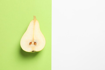 Ripe juicy pear on color background, top view