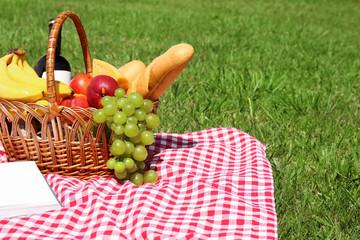 Autocollant pour porte Pique-nique Basket with food on blanket prepared for picnic in park