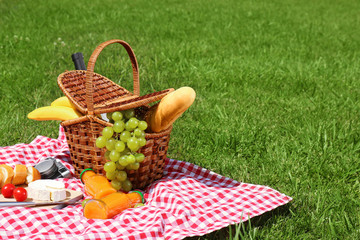 Fotobehang Picknick Basket with food on blanket prepared for picnic in park