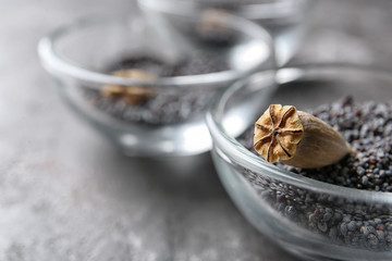 Bowl with dry poppy head and seeds on table, closeup