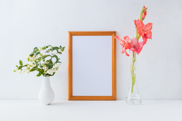 Mockup golden frame and branches with green leaves in a vase on a light background