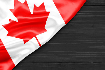 Flag of Canada and place for text on a dark wooden background