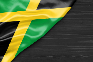 Flag of Jamaica and place for text on a dark wooden background