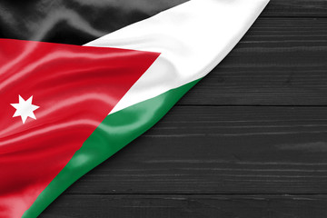Flag of Jordan and place for text on a dark wooden background